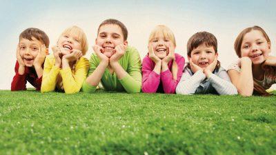 Niños-sonriendo-tumbados-en-el-césped